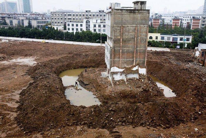 中國昆明這棟公寓樓的租客,承包商挖了一道溝,迫使最後一個家庭出來,必須經過一個護城河。